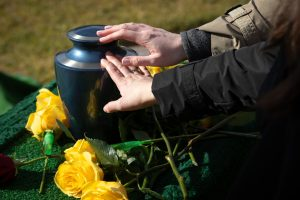 Hands,Touching,A,Burial,Urn,In,A,Bright,Outdoor,Funeral